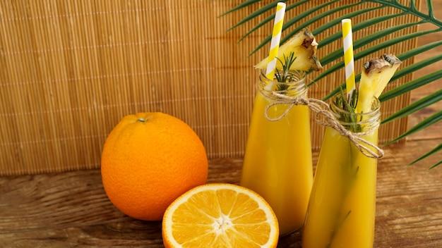 Zwei flaschen tropischer saft mit papierstrohhalmen. orangen, ananas und rosmarin zur dekoration. hölzerner hintergrund.