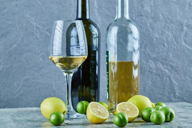 Zwei flaschen und ein glas wein auf marmortisch mit zitronen und kirschpflaumen