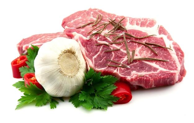 Zwei fleischstücke mit knoblauch, petersilie, pfeffer und trockenem rosmarin