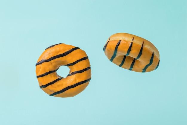 Zwei fliegende orange donuts auf einem blauen hintergrund. beliebtes süßes gebäck.