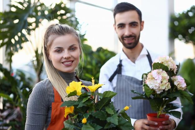 Zwei floristen, die inländisches blumentopf-porträt halten