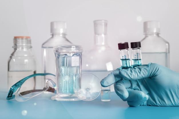 Zwei flüssige proben in plastikfläschchen in behandschuhter hand