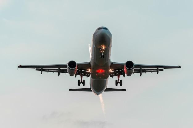 Zwei flugzeuge am himmel, eines im landeanflug vor der landung auf dem flughafen, das andere hoch mit einem kondensstreifen im orangefarbenen sonnenuntergangshimmel.