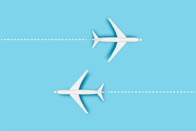 Zwei flugzeuge und eine linie, die die route auf einem blauen hintergrund anzeigt. konzeptreisen, flugtickets, flug, streckenpalette.