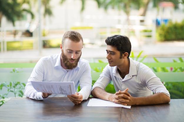 Zwei fokussierte geschäftsleute, die café im im freien treffen und arbeiten