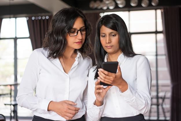 Zwei fokussierte weibliche kollegen, die smartphone im café verwenden.