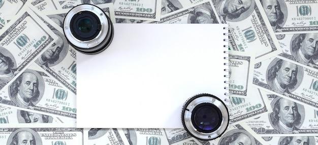 Zwei fotografische objektive und weiße notizbuchlüge