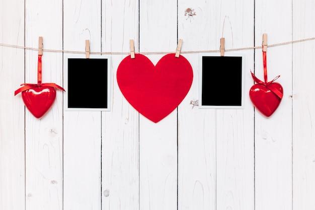 Zwei fotorahmen leer und rotes herz hängen auf weißem holz hintergrund mit platz