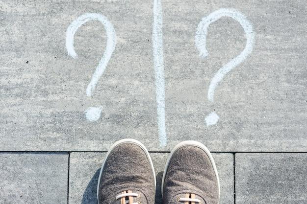 Zwei fragezeichen werden auf einer asphaltstraße handgeschrieben