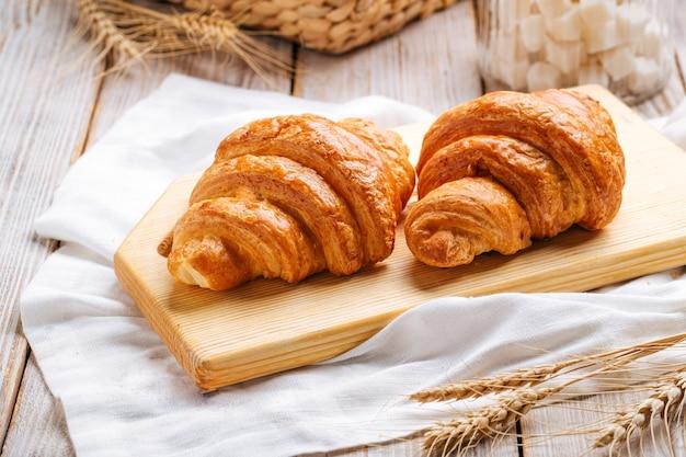 Zwei französische croissants auf dem holzschneidebrett