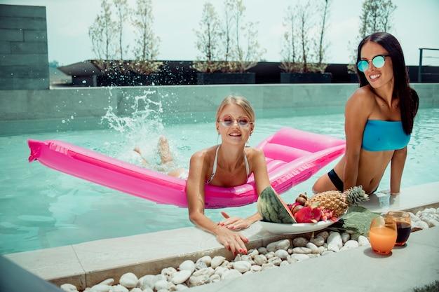 Zwei frau, die auf tropischem luxusurlaub nahe mit großen tellern mit verschiedenen leckeren süßen exotischen früchten im pool, reisen und essen gesunder, veganer vegetarischer lebensstil, diätkonzept entspannt.