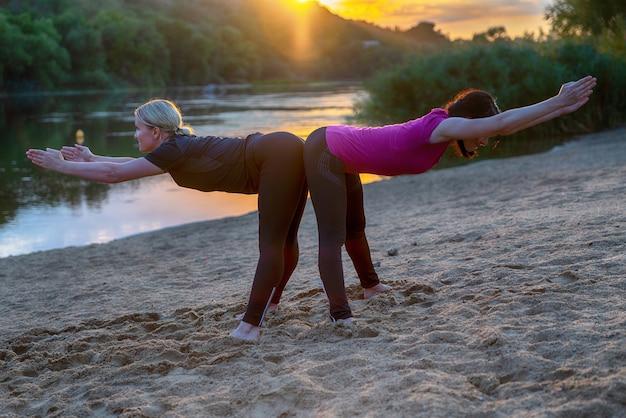 Zwei frau in einer synchronisierten yoga-pose am strand