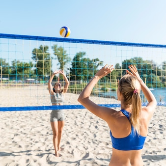 Zwei frauen am strand spielen volleyball