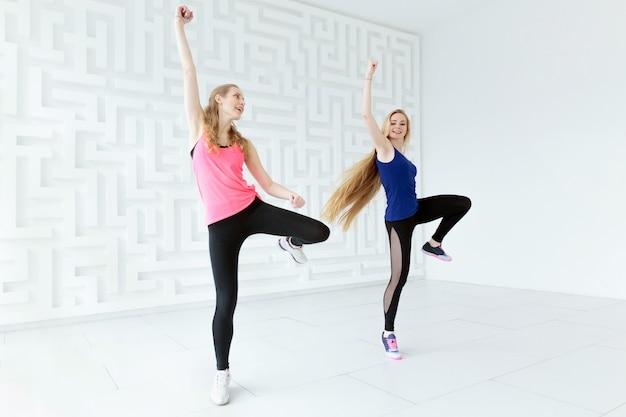 Zwei frauen bei einem kalorienverbrennenden tanz-fitnesskurs