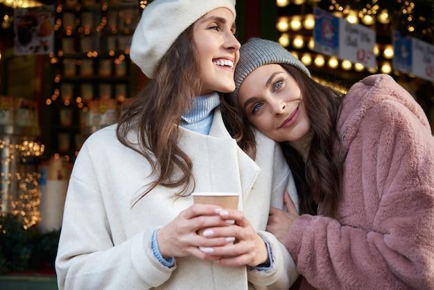 Zwei frauen, die auf weihnachtsmarkt umarmen