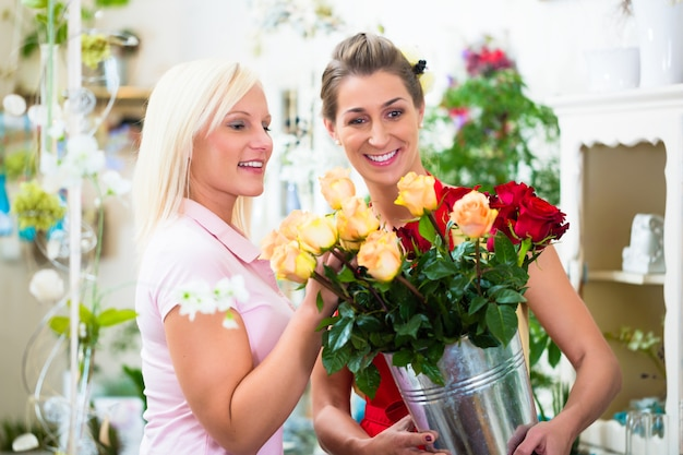 Zwei frauen, die blumenstrauß von rosen im blumenladen betrachten