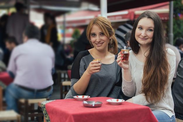 Zwei frauen, die cay, traditionellen türkischen tee, in istanbul trinken