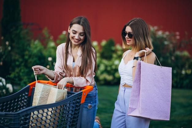 Zwei frauen, die durch den markt mit einkaufswagen kaufen