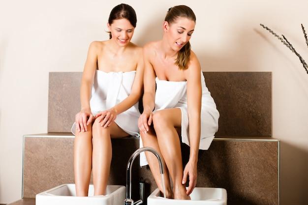 Zwei frauen, die ein fußbad nehmen