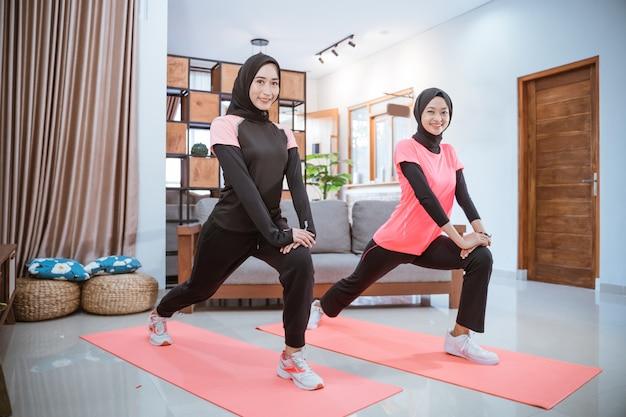 Zwei frauen, die ein kopftuch tragen, lächeln, während sie ausfallschritte machen, während sie zu hause zusammen zu hause trainieren