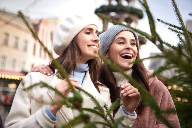 Zwei frauen, die einen perfekten weihnachtsbaum pflücken