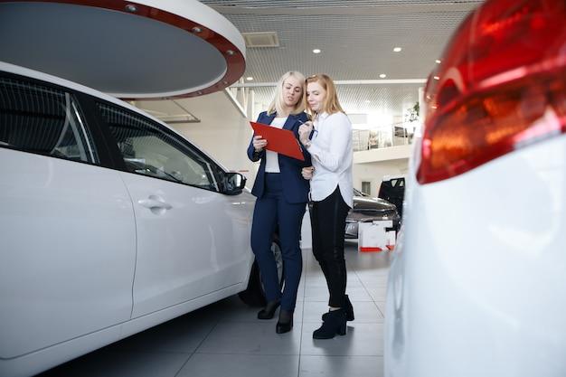 Zwei frauen, die einen vertrag über den kauf eines autos unterzeichnen, wobei sich die verkäuferin durch das offene fenster lehnt und auf den vertrag zeigt