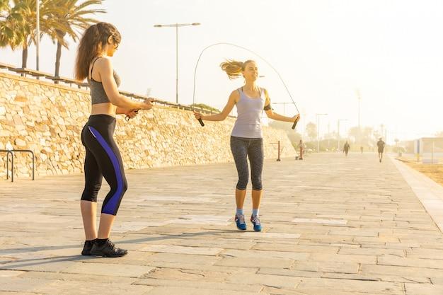 Zwei frauen, die fitnessübungen am meer in barcelona machen