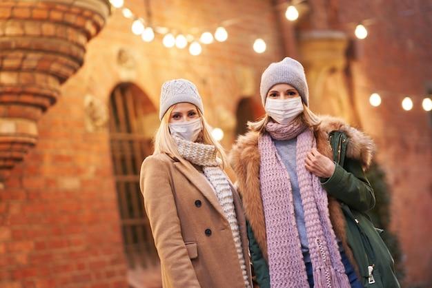 Zwei frauen, die gesichtsmasken tragen und in der stadt rumhängen