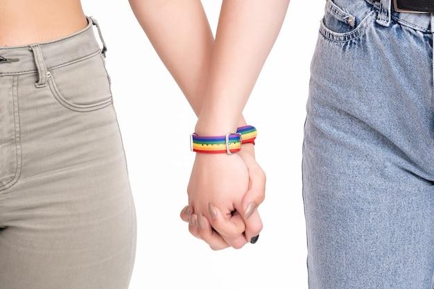 Zwei frauen, die hände mit regenbogenfarbenen lgbt-armbändern auf weiß halten