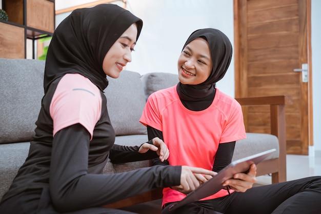 Zwei frauen, die hijab-sportbekleidung tragen, während sie lässig auf dem boden plaudern, während sie ein digitales tablet verwenden, während sie sich zu hause auf das sofa lehnen