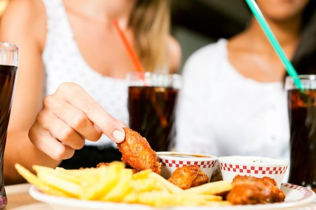 Zwei frauen, die hühnerflügel essen und soda trinken