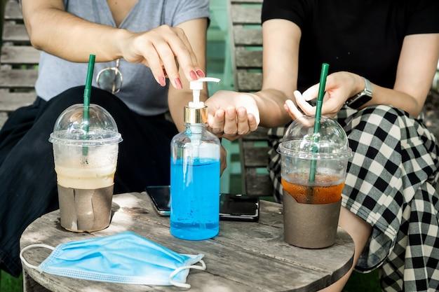 Zwei frauen, die ihre hände mit alkoholgel im café säubern