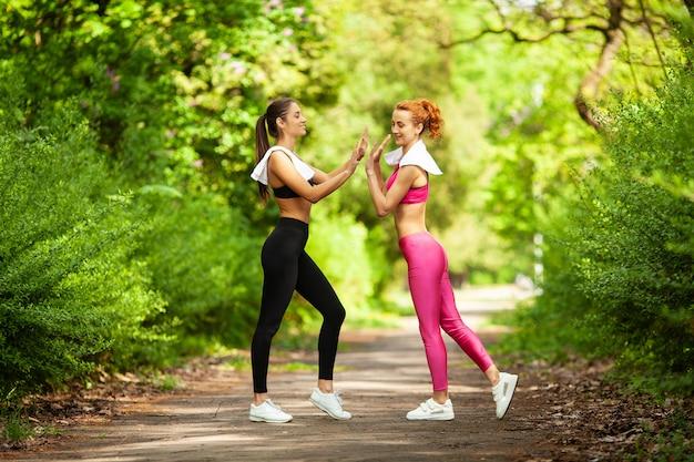 Zwei frauen, die im park trainieren. junge schöne frau, die zusammen übungen draußen tut