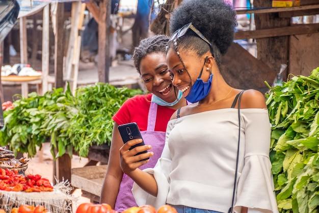 Zwei frauen, die inhalt auf einem telefon in einem lokalen afrikanischen markt betrachten.