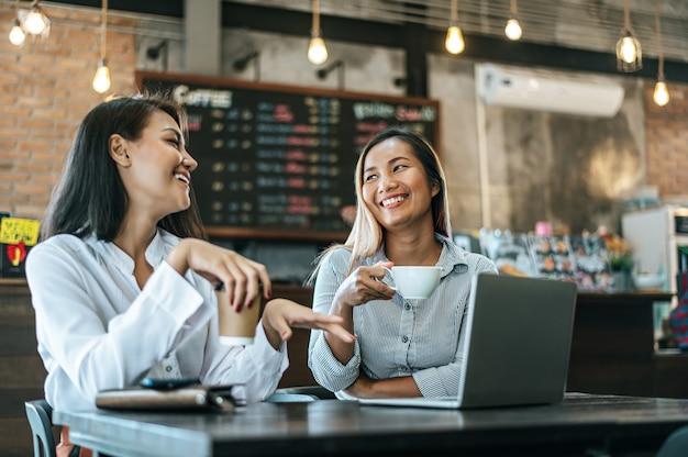 Zwei frauen, die mit einem laptop in einer kaffeestube sitzen und arbeiten
