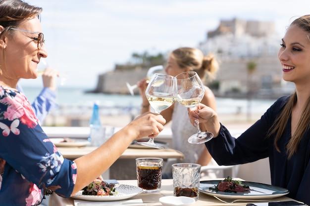 Zwei frauen, die mit gläsern weißwein anstoßen, sitzen an einem tisch in einem strandrestaurant