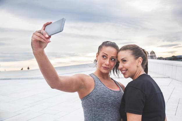 Zwei frauen, die nach dem training ein selfie machen