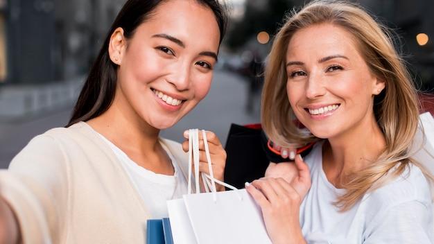 Zwei frauen, die nach einer einkaufssitzung zusammen ein selfie machen