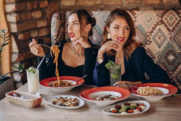 Zwei frauen, die nudeln in einem italienischen restaurant essen