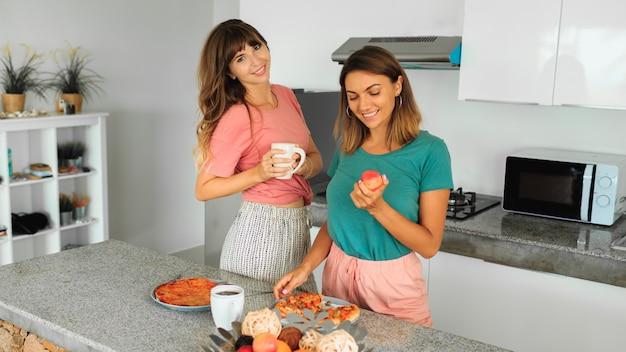 Zwei frauen, die pizza auf küche in der modernen wohnung genießen.
