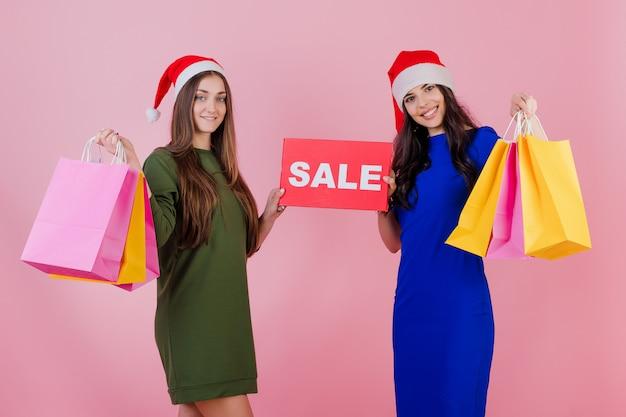 Zwei frauen, die sankt-hüte mit den bunten feiertagseinkaufstaschen und copyspace verkauf tragen, unterzeichnen getrennt über rosa