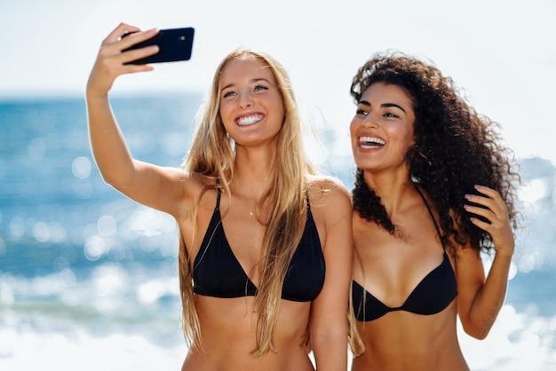 Zwei frauen, die selfie foto mit smartphone im strand machen