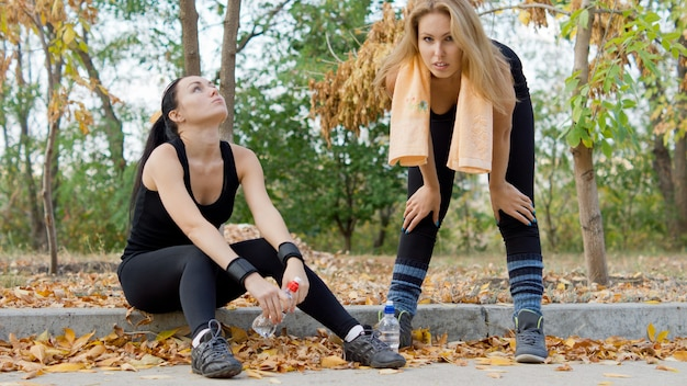 Zwei frauen, die sich am straßenrand mit einer flasche wasser entspannen, nachdem sie im park trainiert haben