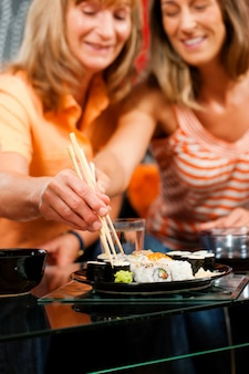 Zwei frauen, die sushi essen
