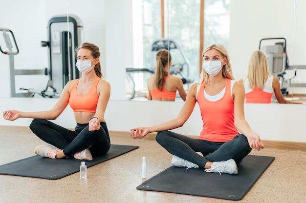 Zwei frauen, die yoga im fitnessstudio mit medizinischen masken tun