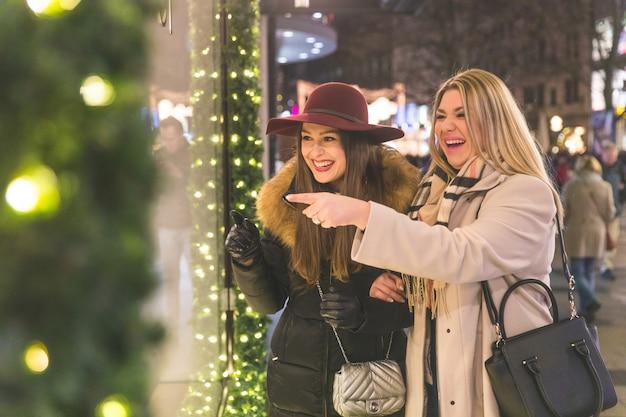 Zwei frauen, die zur weihnachtszeit in münchen einkaufen