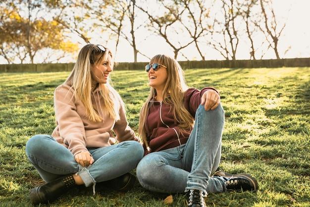 Zwei frauen im freien sitzen auf gras