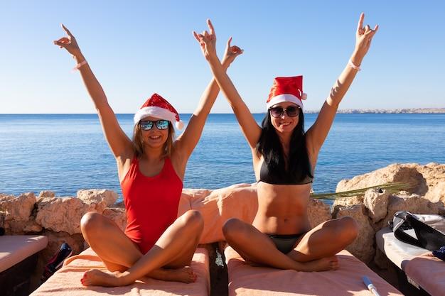 Zwei frauen in badeanzügen und roten weihnachtsmützen feiern weihnachten und neujahr am strand des roten meeres.