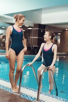 Zwei frauen in den badeanzügen, die nahe dem pool an der turnhalle stehen.