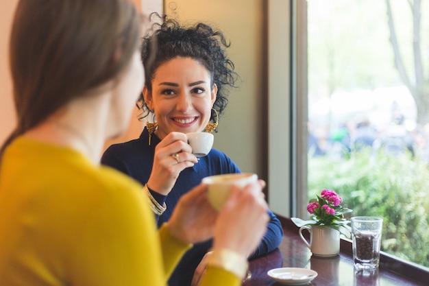 Zwei frauen in einem café, das zusammen kaffee lächelt und trinkt